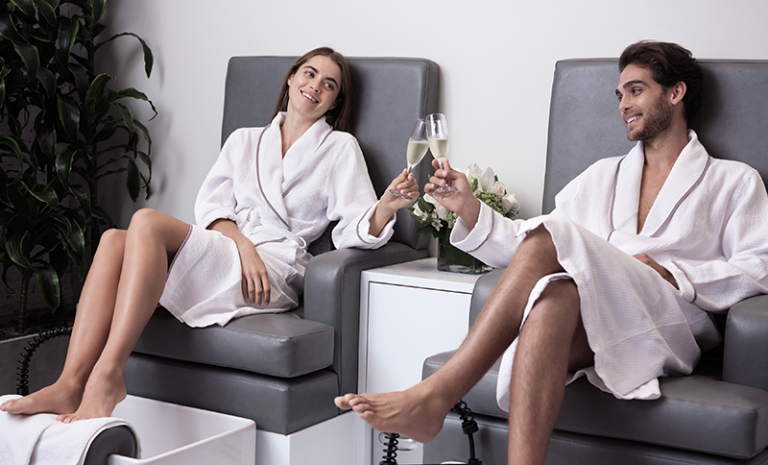 man and woman drinking champagne while getting pedicures